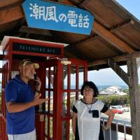 Tomohiko Kutsuna and his wife, Kazuko, stand in front of a telephone booth they set up on a hill in Tahara, Aichi Prefecture, as a place to speak to a prior student who took her own life in 2009. | CHUNICHI SHIMBUN
