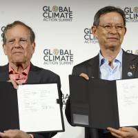 Takejiro Sueyoshi (right) of the Japan Climate Initiative and America's Pledge Vice Chairman Carl Pope sign a partnership in San Francisco on Thursday. | KYODO