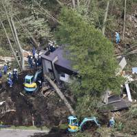 Rescuers search for people trapped under a collapsed house in the town of Atsuma, Hokkaido, on Thursday. | KYODO