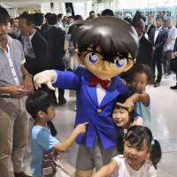 Children play with a person dressed as the Conan Edogawa character at Tottori Sand Dunes Conan Airport in Tottori Prefecture on July 28. | KYODO