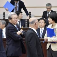 Kumamoto Municipal Assembly member Yuka Ogata is surrounded by fellow assembly members Friday after being criticized for asking questions from the podium while sucking on a cough drop. | KYODO