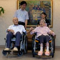 Masao Matsumoto (left) and Miyako Matsumoto, confirmed as the world's oldest living married couple by Guinness World Records, pose for a photo with a great-grandchild and care staff at a nursing house in Takamatsu, Kagawa Prefecture, on Tuesday. | REUTERS