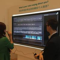 A participant speaks to a device that analyzes a person's voice, sex, height, skull type, personality and emotional state during the World Economic Forum's Annual Meeting of the New Champions in Tianjin, China, on Sept. 19. | SAYURI DAIMON