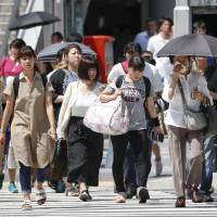 People walk in scorching weather in Nagoya in August. | KYODO