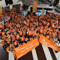 Participants of the Run Tomo event pose in the city of Chiba on Sunday. The goal of the event is to improve social inclusion for people with dementia. | YOSHIAKI MIURA