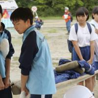Junior high school students carry a stretcher during a disaster drill in the town of Shichigahama, Miyagi Prefecture, on Saturday. | KYODO