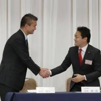 Yuichiro Tamaki (right), who was elected Tuesday to head the Democratic Party for the People, the nation's second-largest opposition party, shakes hands with contender Keisuke Tsumura before the vote begins at a Tokyo hotel the same day. | KYODO