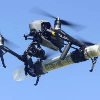 A drone delivers newspapers in Asahikawa, Hokkaido, on Friday as part of a trial aimed at finding ways to deliver news in times of disaster. | KYODO
