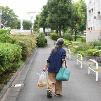 A woman carries grocery bags while walking past buildings at the Tama New Town residential development in Tama, western Tokyo, on Tuesday. As society ages and the government cuts social welfare spending, older women are bracing for the impact. | BLOOMBERG
