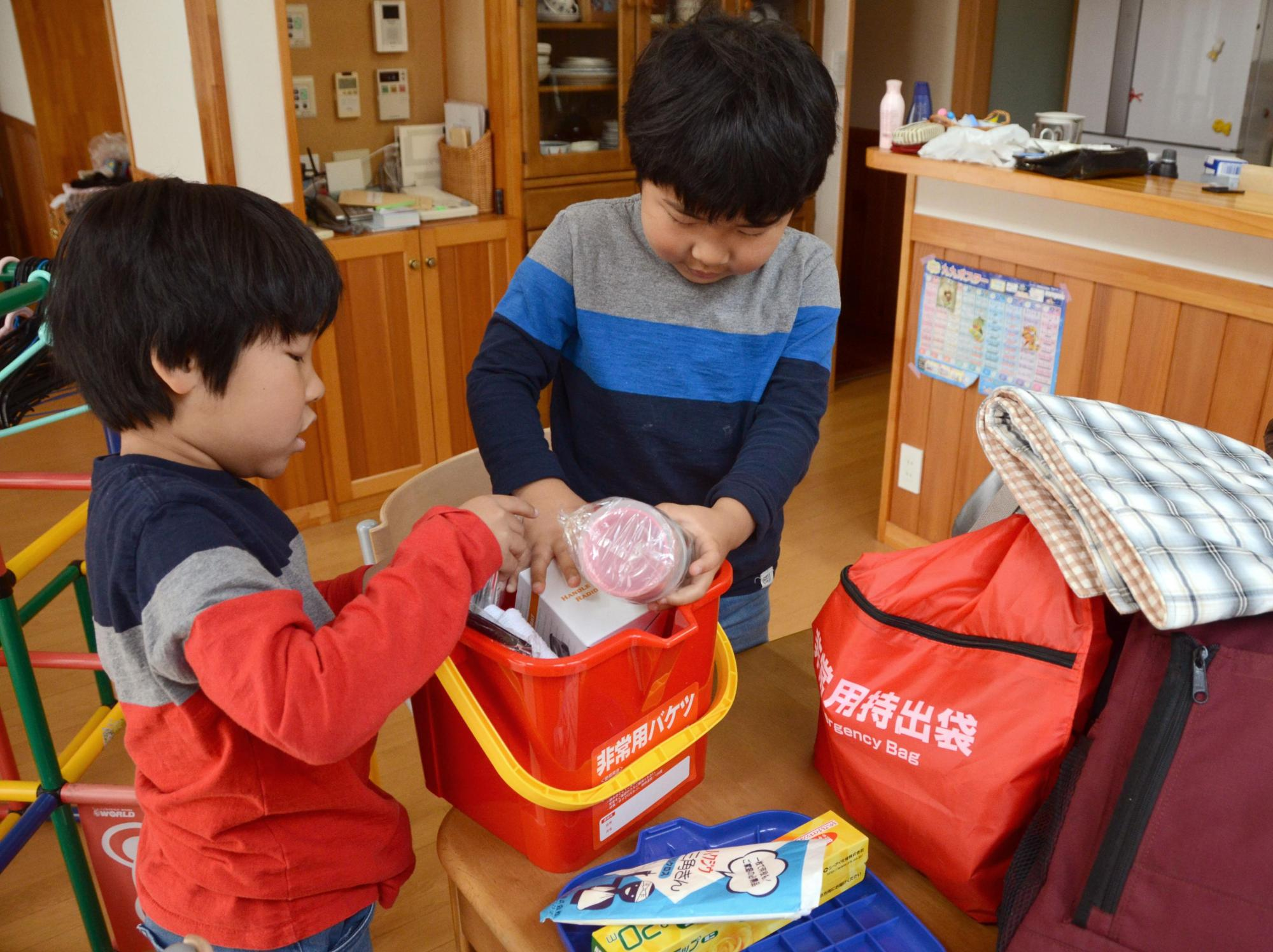 Young brothers check an emergency kit in Ainan, Ehime Prefecture, in April 2014. Among people who took an online survey in July, 65 percent do not have such a kit. | KYODO
