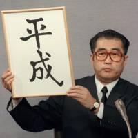 Then-Chief Cabinet Secretary Keizo Obuchi holds up the kanji for the new era name Heisei on Jan. 7, 1989, the day Emperor Hirohito died. | KYODO