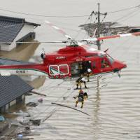 Rescuers hoist up a resident on July 7 of a badly flooded area of Kurashiki, Okayama Prefecture, following torrential rains that hit a wide area of western Japan. | KYODO