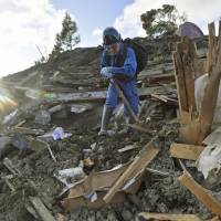 A man searches for his late great-grandmother's photo in Atsuma, Hokkaido, on Sept. 13, a week after a strong earthquake hit. | KYODO