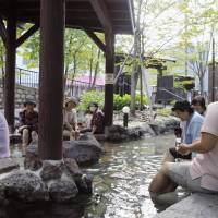 People take a foot bath in the Jozankei Onsen hot spring district in Sapporo on Tuesday. The government plans to subsidize discounts for hotel room and other accomodations in Hokkaido to help bring tourists back to the disaster-hit prefecture. | KYODO