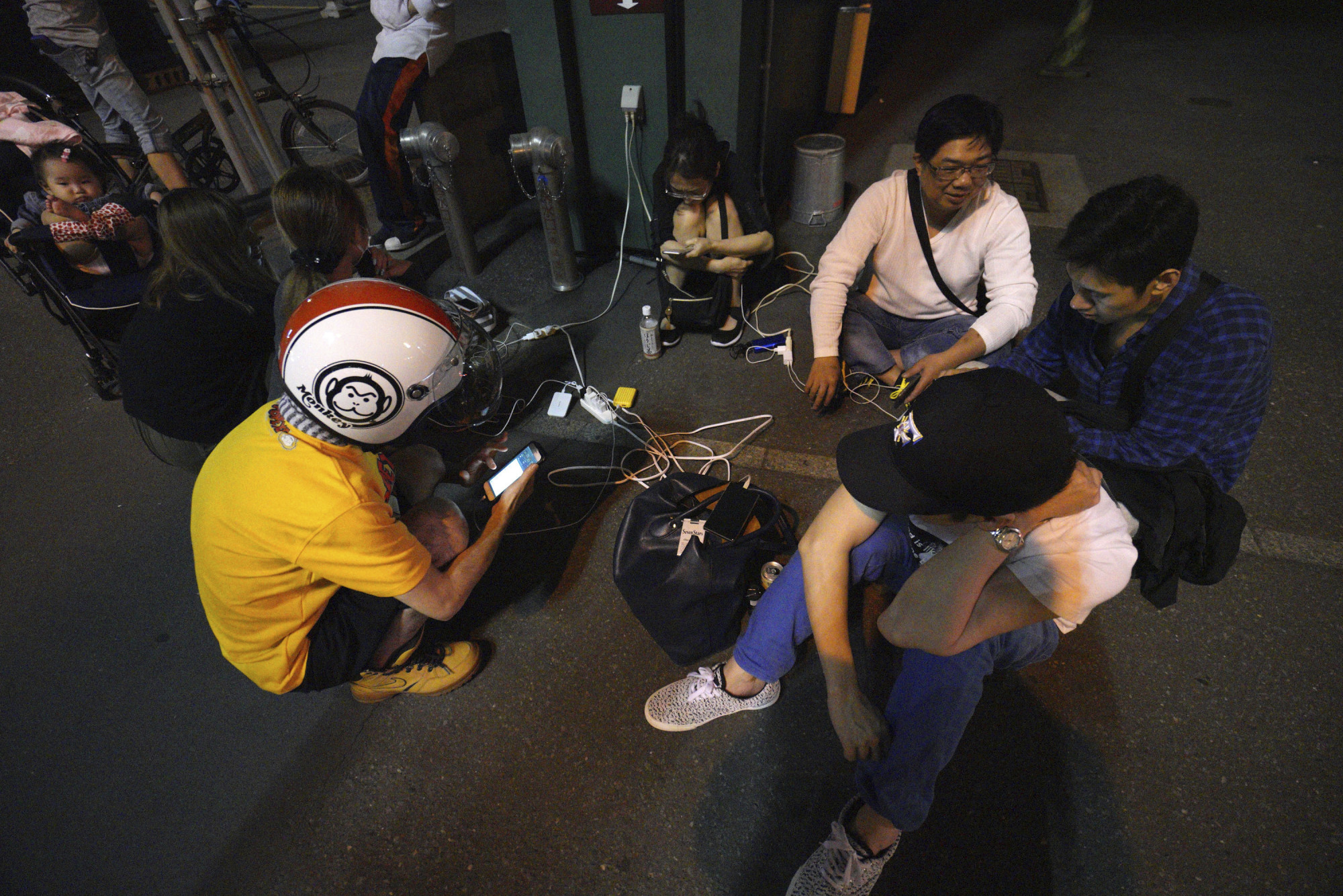 People gather to charge their mobile phones during a blackout in Sapporo on Sept. 6 after a powerful earthquake hit Hokkaido, triggering landslides as well as causing the loss of power.