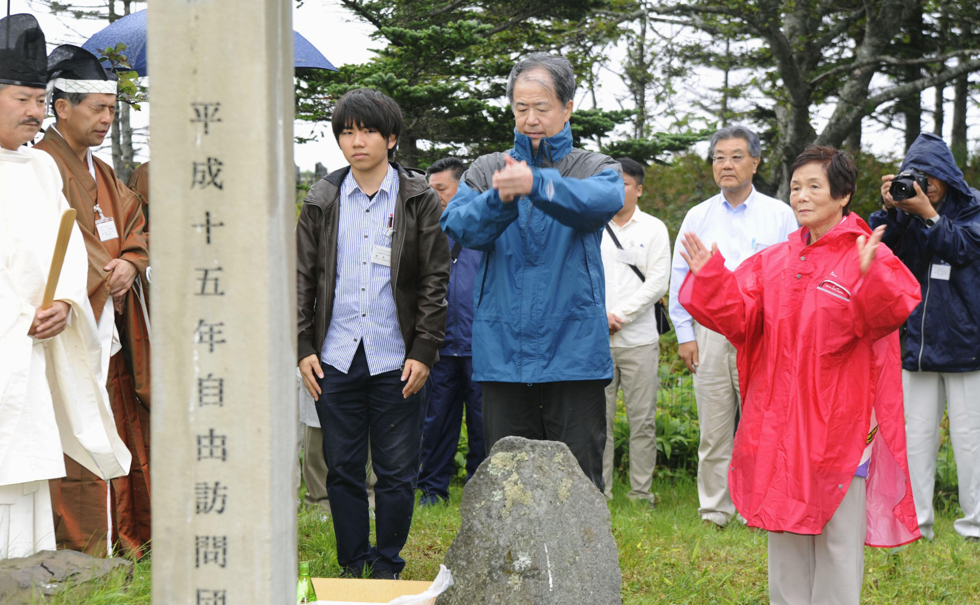 Chizuko Yamaguchi (right), Osamu Okada (second from right) and Kakeru Nemoto visit a Japanese graveyard on Kunashiri Island in August. | KYODO
