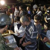 People line up to receive food supplies handed out by Self-Defense Force members Thursday at an evacuation center in Atsuma, Hokkaido. | KYODO