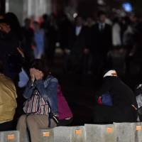 People gather on a street in Sapporo's Chuo Ward early Thursday morning as the area suffers a blackout following a big earthquake. | KYODO