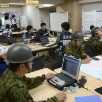 Rescue team and other officials gather information in the Hokkaido Prefectural Government building Thursday morning following a major earthquake. | KYODO