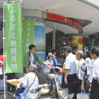 A group of municipalities hold an event in Tokyo's Chiyoda Ward on Aug. 1 to promote furusato nōzei, a tax donation system aimed at providing financial support for rural areas.   KYODO