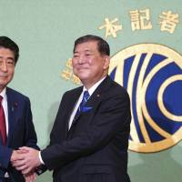 Prime Minister Shinzo Abe, current president of the ruling Liberal Democratic Party, and former defense chief Shigeru Ishiba shake hands in Tokyo on Friday prior to a debate ahead of the Sept. 20 LDP presidential election. | AP