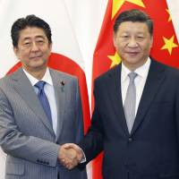 Prime Minister Shinzo Abe and Chinese President Xi Jinping shake hands during their meeting in Vladivostok, Russia, on Wednesday. | KYODO