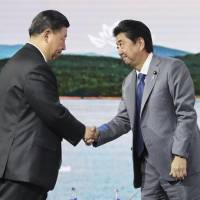 Prime Minister Shinzo Abe and Chinese President Xi Jinping shake hands during the Eastern Economic Forum in Vladivostok, Russia, on Sept. 12. | POOL / VIA KYODO