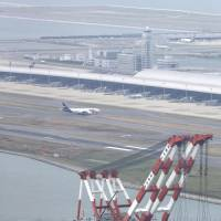 A runway at Kansai International Airport that reopened Friday is seen with the damaged bridge in the foreground. | KYODO