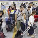 Foreign visitors arrive at Kansai airport's train station on Tuesday, the day the trains resumed operation.