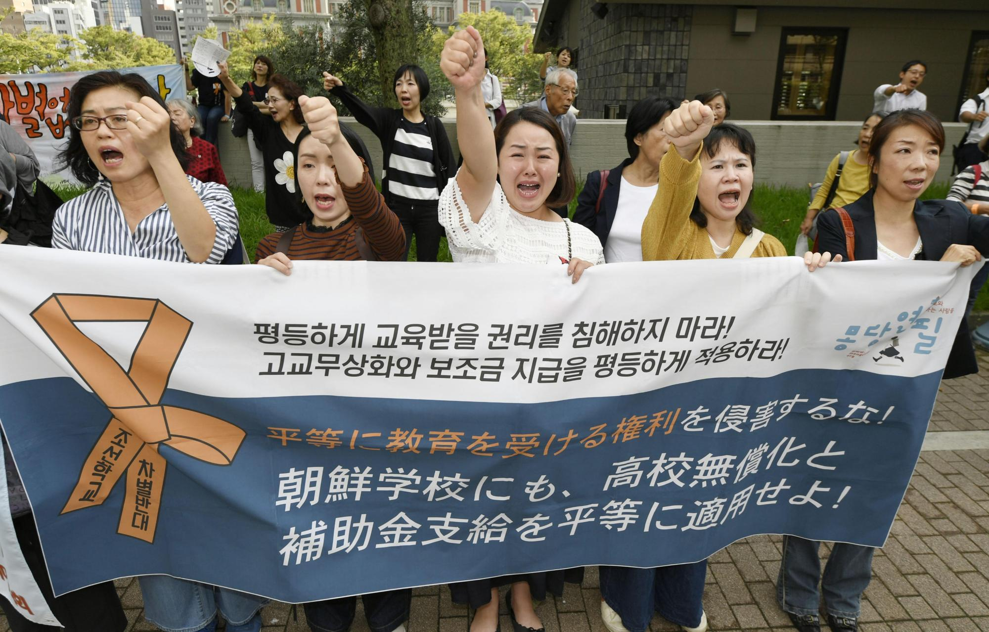 Supporters of Korean schools who oppose the government's decision to deny the institutions access to tuition subsidies stand in front of the Osaka High Court on Thursday, protesting the court's decision that a Korean school in Osaka is not eligible to receive the subsidies. | KYODO