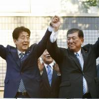 Prime Minister Shinzo Abe (left) and former Defense Minister Shigeru Ishiba pose after giving campaign speeches in the city of Saga on Saturday ahead of the Liberal Democratic Party's presidential election on Sept 20 . | KYODO