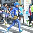 A costumed runner runs along with other participants during the Tokyo Marathon in February 2016.