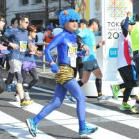 A costumed runner runs along with other participants during the Tokyo Marathon in February 2016. | YOSHIAKI MIURA