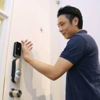 Takashi Hamamichi, president of information technology company Otafuku Lab Inc., uses a microchip implanted in his hand to open a door in Osaka in August. | KYODO