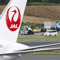 Investigators gather at Narita airport in Chiba Prefecture on Thursday after an unexploded shell was found buried near a runway. | KYODO