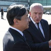 Crown Prince Naruhito is welcomed by French Interior Minister Gerard Collomb at Lyon's airport on Friday. | AP