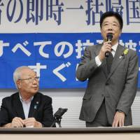 Katsunobu Kato, the Cabinet minister in charge of the abduction issue, right, speaks at an event in Tokyo in June calling for the return of Japanese nationals who were abducted by North Korean agents decades ago. | KYODO