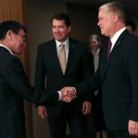 Foreign Minister Taro Kono shakes hands with U.S. Special Representative for North Korea Stephen Biegun as U.S. Ambassador to Japan William Hagerty looks on during their meeting in Tokyo on Friday. | REUTERS