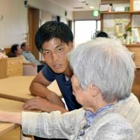 Hiroki Murai, a member of the semipro soccer team Banditonce Kakogawa in Hyogo Prefecture, speaks to a resident of the nursing home where he works in the city of Ono on Aug. 9. | KYODO