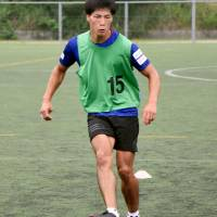 Hiroki Murai, a member of Banditonce Kakogawa, a soccer team in Hyogo Prefecture, practices Aug. 9 after finishing his shift at a nearby nursing home. | KYODO