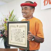 Haruo Obata is honored by the town of Hiji, Oita Prefecture, on Monday for his actions and spirit of volunteerism. | KYODO