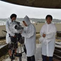 Jinshiro Motoyama (right) is interviewed by filmmakers Shinya Todori (second from right) and Takuya Todori (third from right) at Kakazutakadai Park in Ginowan, Okinawa Prefecture, on Aug. 15. | THE OKINAWA TIMES
