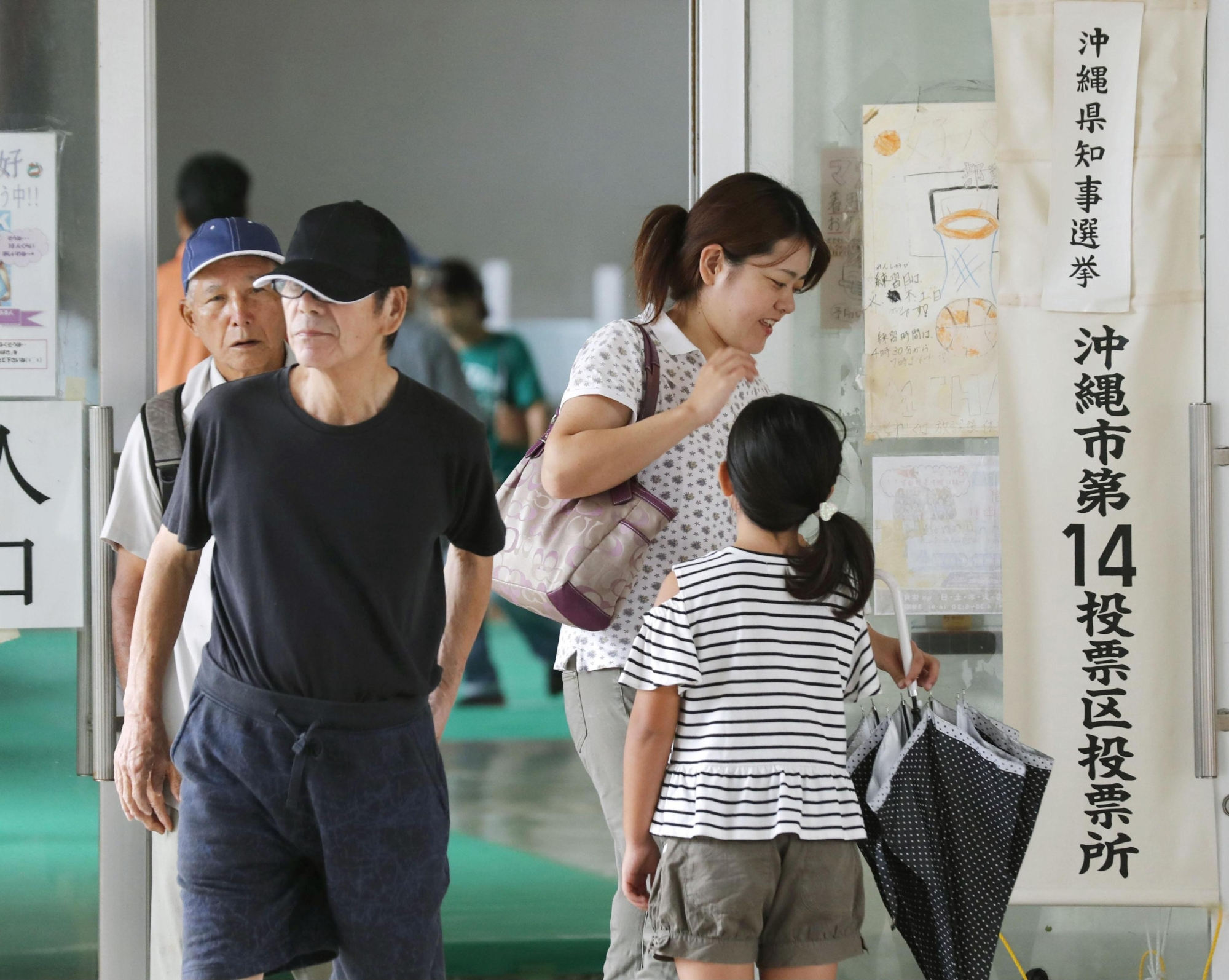 Voters leave a polling station in the city of Okinawa early Sunday. | KYODO