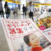 Leaflets soliciting volunteers for the 2020 Tokyo Olympics are distributed Wednesday near Shinjuku Station. | KYODO