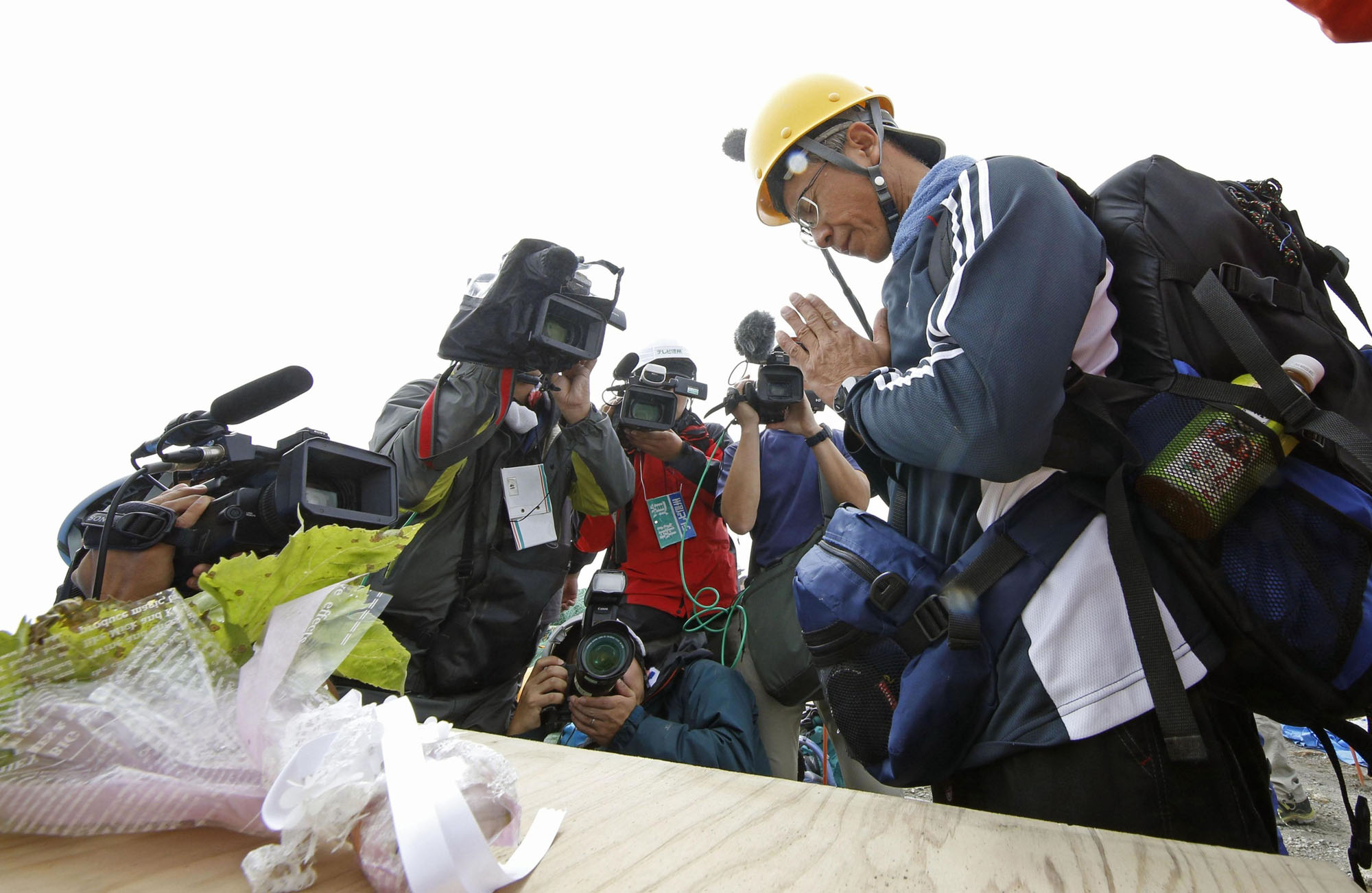 A man who lost a family member when Mount Ontake erupted four years ago offers a prayer Wednesday near the mountain's summit. | KYODO