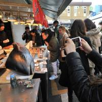 A tourist takes a photo of the head of a tuna fish at a shop in the Tsukiji outer market, located just outside the famous wholesale fish market in Chuo Ward, Tokyo, in January 2017. While the inner market is soon to be relocated to the nearby Toyosu area, shops at the outer market will remain. | YOSHIAKI MIURA