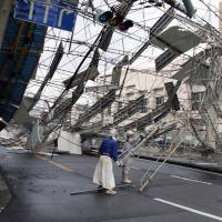 Scaffolding is blown down by winds from the powerful Typhoon Jebi on Tuesday in Nishinari Ward in Osaka city. | KYODO