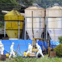 Officials disinfect a farm in the city of Gifu on Sunday after a pig that died there was confirmed as having swine fever. | KYODO