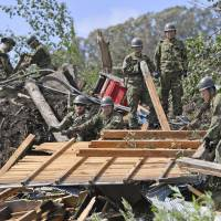 Self-Defense Forces members perform search operations in an area affected by landslides in the town of Atsuma, Hokkaido, after a powerful earthquake rocked the region. | KYODO