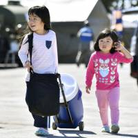 Children carry water from an evacuation center to their home on Tuesday in Atsuma, the town in Hokkaido hit hardest by Thursday's earthquake. | KYODO